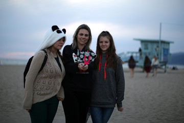 Camila Breda, 39, and her daughters Giovanna Kreischer, 13, and Alexia Kreisher, 12, hold a selfie stick as they pose for an iPhone photo by the Pacific Ocean on a cold spring solstice day in Santa Monica