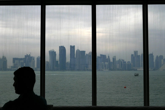A man sits inside the Islamic art museum of Doha as the city's skyline is seen in the background in Doha