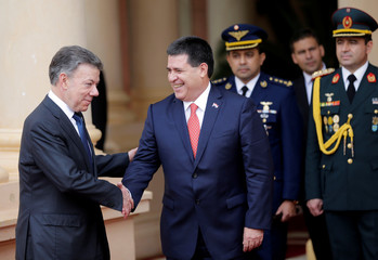 Paraguay's President Horacio Cartes and Colombia's President Juan Manuel Santos shake hands in front of the Lopez Presidential Palace in Asuncion