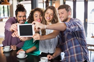 Friends taking selfie with digital tablet in restaurant