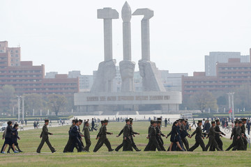 Soldiers walk in front of the Monument to the Foundation of the Workers' Party in Pyongyang