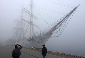 A man takes a picture of Dar Pomorza sailing ship as thick fog covers the Port of Gdynia