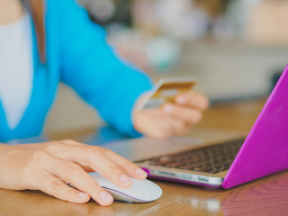 Pretty Young womans hands holding a credit card and using tablet, smartphone and laptop computer for online shopping. Online payment. Female working on smart phone laptop in a cafe.