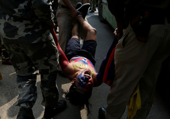 A Tibetan reacts as he is detained by police during a protest held to mark the 58th anniversary of the Tibetan uprising against Chinese rule, outside the Chinese embassy in New Delhi