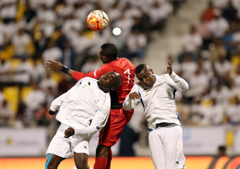 Migrant workers playing for Nakheel Landscapes (in white) fight for the ball with a migrant worker playing for Al Asmakh Facilities Management during their final soccer match at the Workers' Cup in Doha