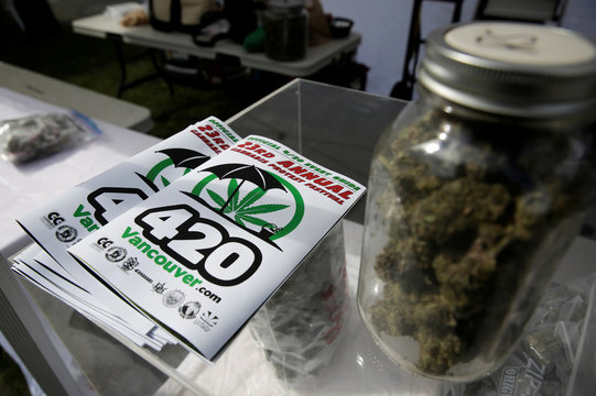A program and a jar filled with marijuana buds are pictured at the annual 4/20 marijuana event at Sunset Beach in Vancouver