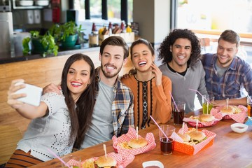 Woman taking selfie with cheerful friends in restaurant