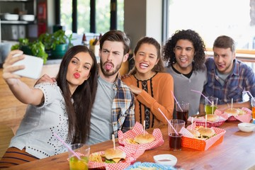 Woman taking selfie with friends in restaurant