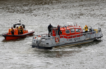 Emergency services patrol after a man fell off  Westminster Bridge into the Thames in London