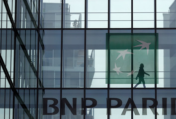 A woman is seen in silhouette as she walks behind the logo of BNP Paribas in a building in Issy-les-Moulineaux, near Paris
