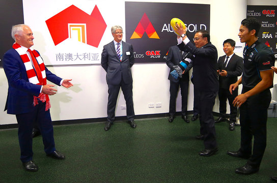 Australia's Prime Minister Malcolm Turnbull passes a ball to Chinese Premier Li Keqiang as Port Adelaide player Chen Shaoliang from China, during a visit to the team's room before the start of an AFL game at the SCG in Australia