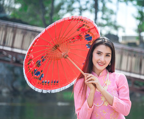 Asian girl wearing pink Ao Dai carry red umbrella..Portrait of Vietnamese girl traditional dress, Ao dai is famous traditional costume for woman in Vietnam