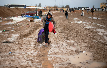 A displaced Iraqi makes his way to get into Hamam al-Alil camp, on a rainy day, south of Mosul