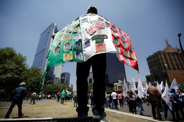 A man carries a Mexican flag with pictures of some of the 43 missing students during a protest to demand justice for the 43 missing students of Ayotzinapa College Raul Isidro Burgos, in Mexico City, Mexico