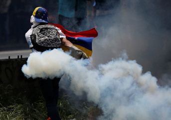 A demonstrator carries a tear gas canister during clashes with security forces during an opposition rally in Caracas