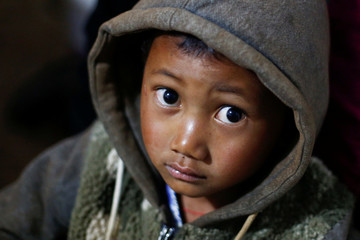 A refugee boy who fled with his family fighting in neighbouring Myanmar rests in the house of a relative in the village of Baiyan near Nansan