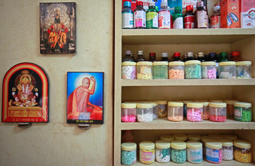 FILE PHOTO: Pictures of Hindu gods hanging beside a medicine rack inside a clinic in Pune