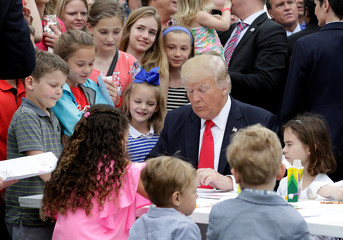 Children watch U.S. President Donald Trump makes an Easter greeting card that will be sent to a member of the military at the 139th annual White House Easter Egg Roll on the South Lawn of the White House in Washington