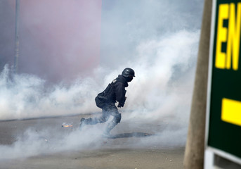 A riot policeman runs among tears gas during a clash with Coca growers from Yungas in La Paz