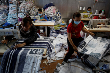 People work at a private factory which produces blankets outside Hanoi, Vietnam