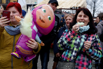 """Spectators watch as revellers take part in a traditional event marking the last day of the carnival season, called """"Kusaki"""", in the village of Jedlinsk near Radom"""