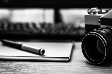 Still life of photographer desk in home office interior. Professional photo media working equipment, camera body, lenses, monitor and tablet