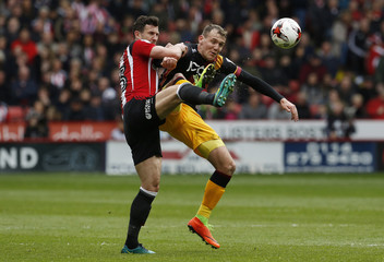 Sheffield United's Jake Wright (L) in action with Bradford City's Charlie Wyke