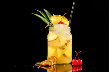 Fresh pineapple cocktail in jar decorated with cherry and ice isolated at black background.