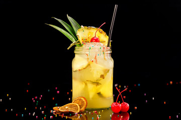 Fresh pineapple cocktail in jar decorated with cherry and colorful candies isolated at black background.