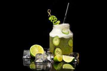 Jar with cucumber cocktail decorated with lime and ice cubes isolated at black background.