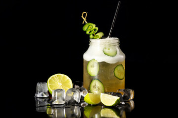 Closeup image of jar with cucumber cocktail decorated with lime isolated at black background.
