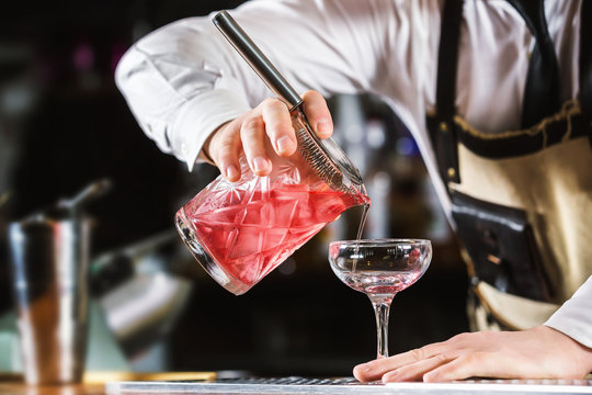Male bartender is making cocktail pouring alchohol from jug to glass at bar background.