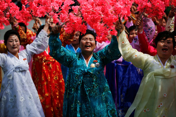Women wearing traditional clothes react as they march past a stand during a military parade marking the 105th birth anniversary of country's founding father in Pyongyang