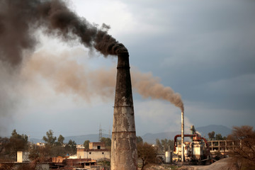 Smoke rises from the smoke stacks of asphalt and brick factories burning coal, old shoes and oil extracted from tyre rubber and plastic in Islamabad