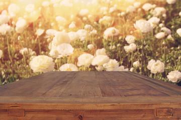 wooden board table in front of summer flowers field