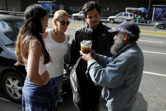 Diego Prada and Maria Luisa Pombo, Volunteers of the Make The Difference (Haz La Diferencia) charity initiative, speak with a homeless man after giving him a cup of soup and an arepa in Caracas