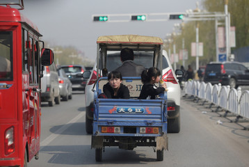 A woman and her daughter are carried by a motor tricycle on a street in Xiongxian county