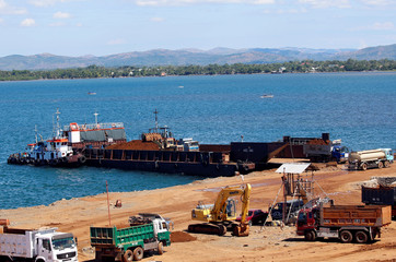 A port is pictured as trucks and a back hoe load rocks and soil containing nickel-ore minerals into a barge in the mining town of Sta Cruz Zambales