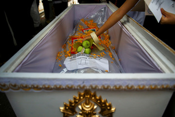 A medical student places flowers on a cadaver during a religious ceremony to pay respects to cadavers used during their medical studies before the bodies are removed from Chulalongkorn Hospital in Bangkok