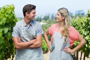 Happy couple looking at each other while standing in vineyard