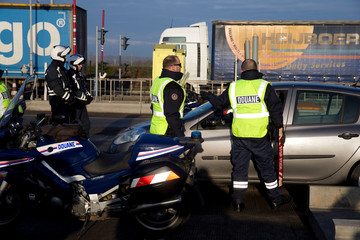 French customs officers stand along the highway to check vehicles and verify the identity of travellers on the A1 motorway between France and Belgium at Fresnes les Montauban toll near Arras