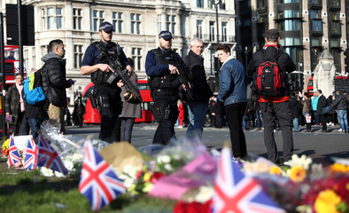 Armed police officers pass tributes in Parliament Square following a recent attack in Westminster, London