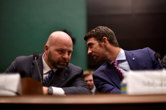 Olympic gold medalist Phelps whispers to Olympic gold medalist Nelson as they testify before the House Oversight and Investigations Subcommittee about anti-doping policy in international sport in Washington