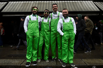 People dressed in green outfits pose for a picture during the St. Patrick's day parade in Dublin