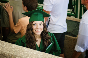 Happy beautiful girl with hat and gown graduates at ceremony graduation