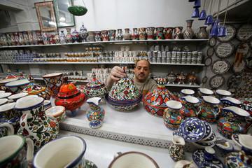 Palestinian man arranges ceramics in Al-Okhowa pottery shop in the West Bank city of Hebron
