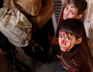A boy injured during a battle between Iraqi troops and Islamic state fighters stand inside a house before he was rescued by Iraqi special forces in Mosul