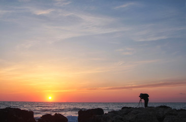 Silhouette of a photographer with a backpack and tripod with a beautiful sea sunset on the background