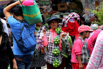 Woman sells vegetables at San Roque market in Quito