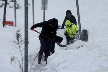 Men shovel snow during a snowstorm in the village of Nyack